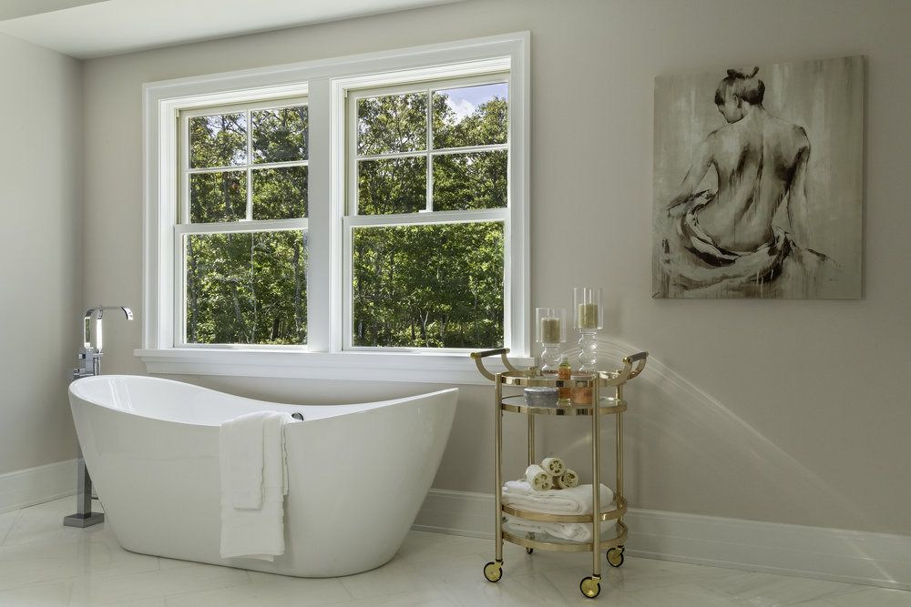 Spacious bathroom with oval shaped plunge bathtub and copper colored wheeled towel cart