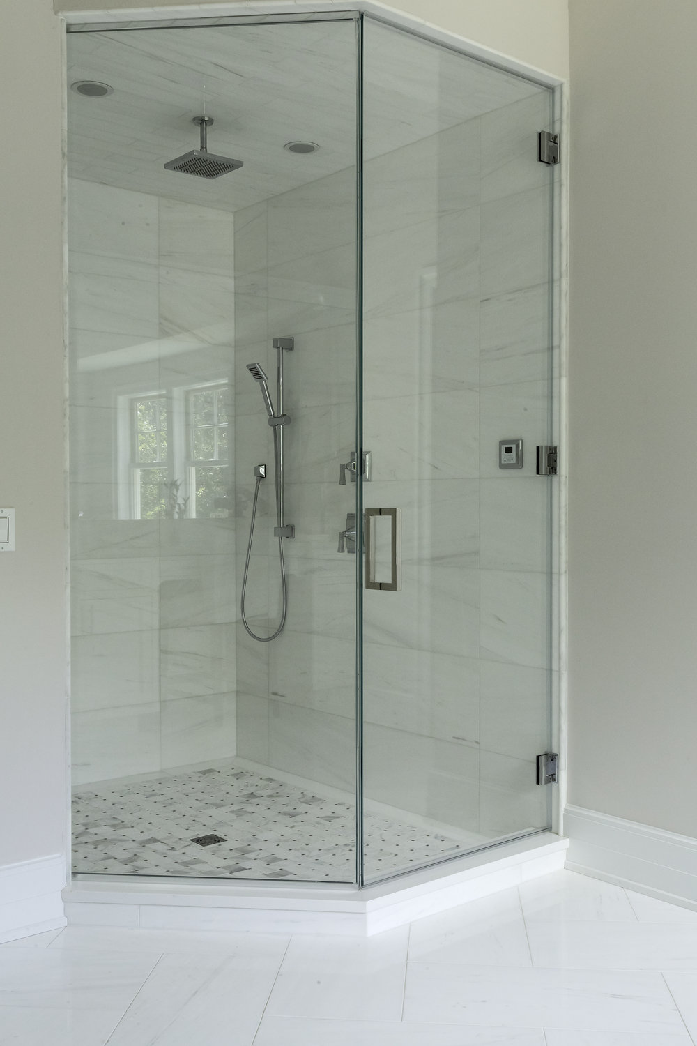Glass walled standing shower with hanging shower head