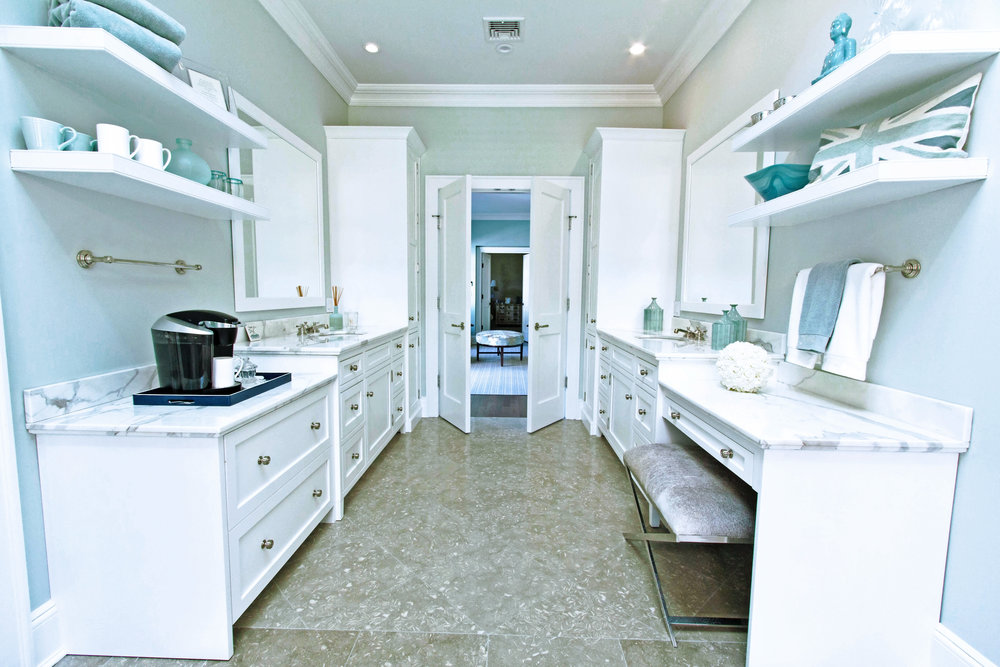 Long bathroom with double doors and counters on both sides
