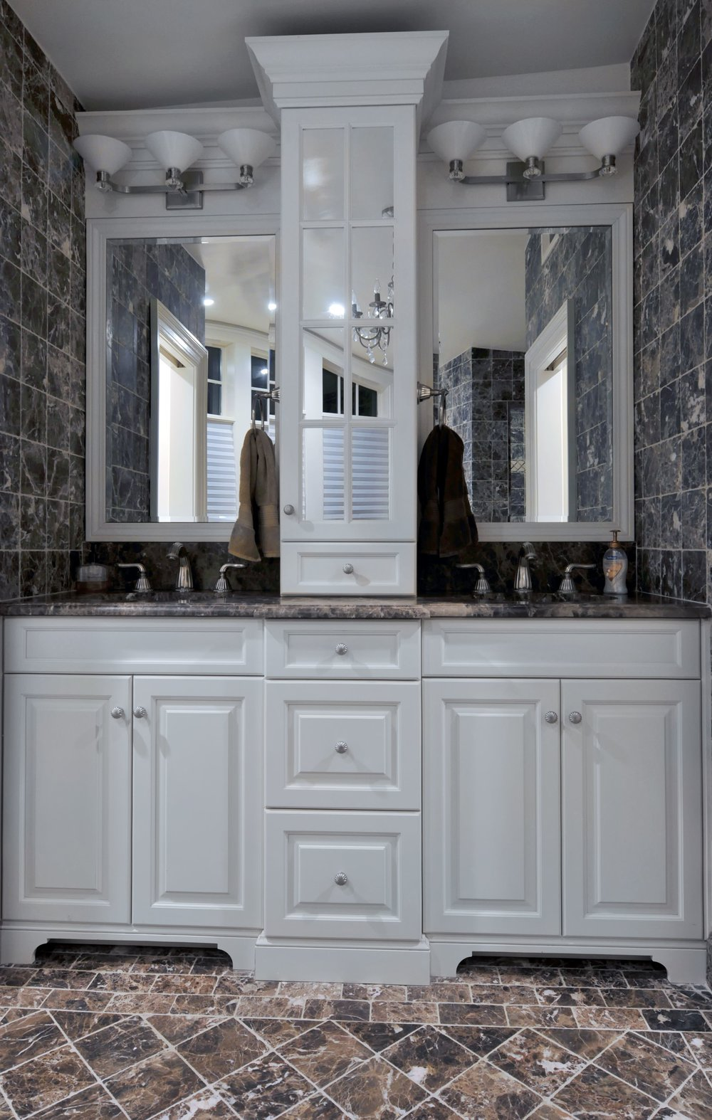 Bathroom with dark tie and double sinks with mirrors above