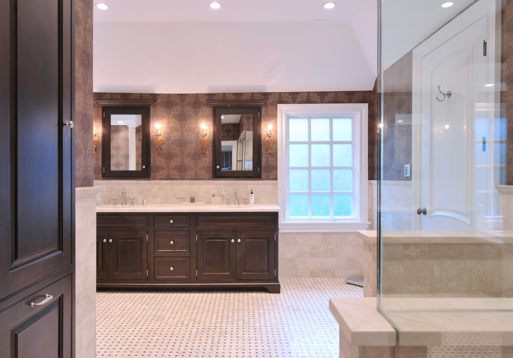 Traditional style bathroom with tiled floor and walls and deep brown wood detail
