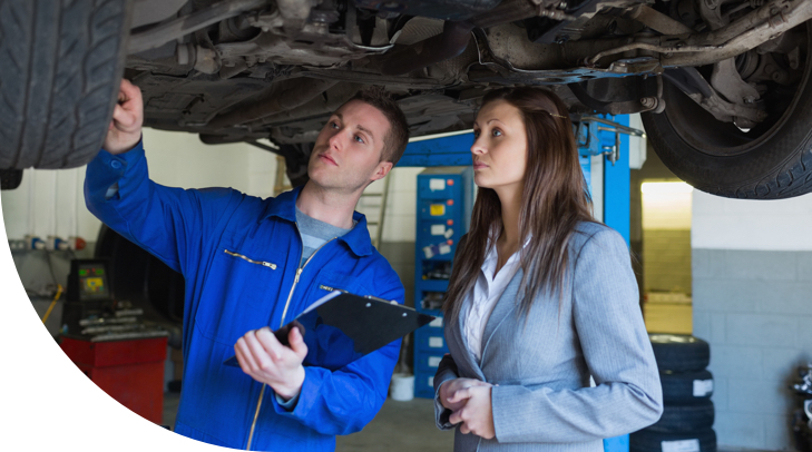 car on automotive lift while male mechanic reviews wheel alignment with female customer.jpg