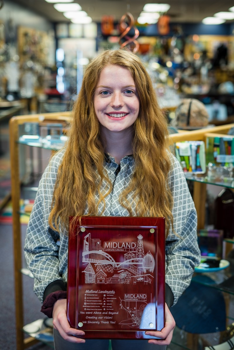 Izzy Waldie poses with her artwork laser-engraved on a glass frame by Wellington Ltd in Midland