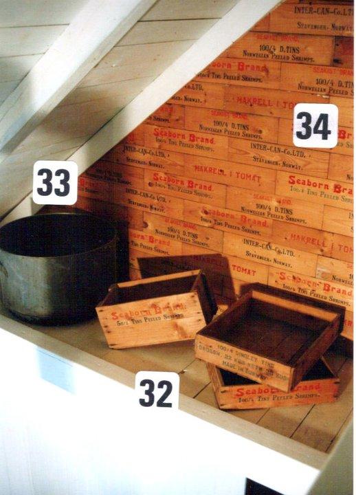 Fra Galleri driften på 80 tallet. Gamle originale sjablongmalte trekasser og kassebord brukt som veggdekorasjon på loftet. Kassene ble brukt til å pakke hermetikken for frakt og eksport.