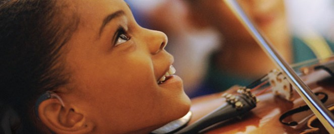 Hearing aid girl playing & smiling.jpg