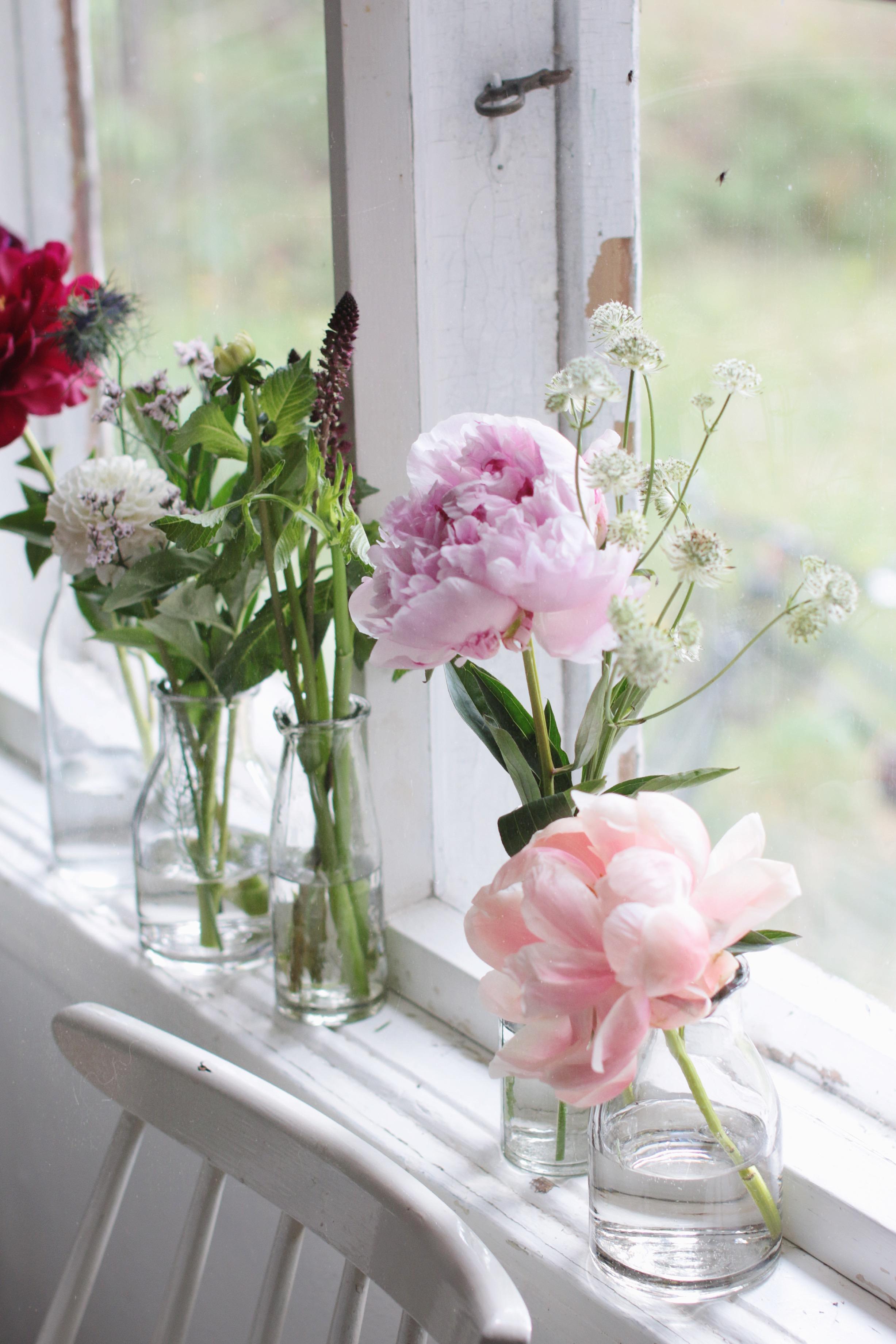 Pionia ja muita kesäkukkia rennossa kukka-asetelmassa