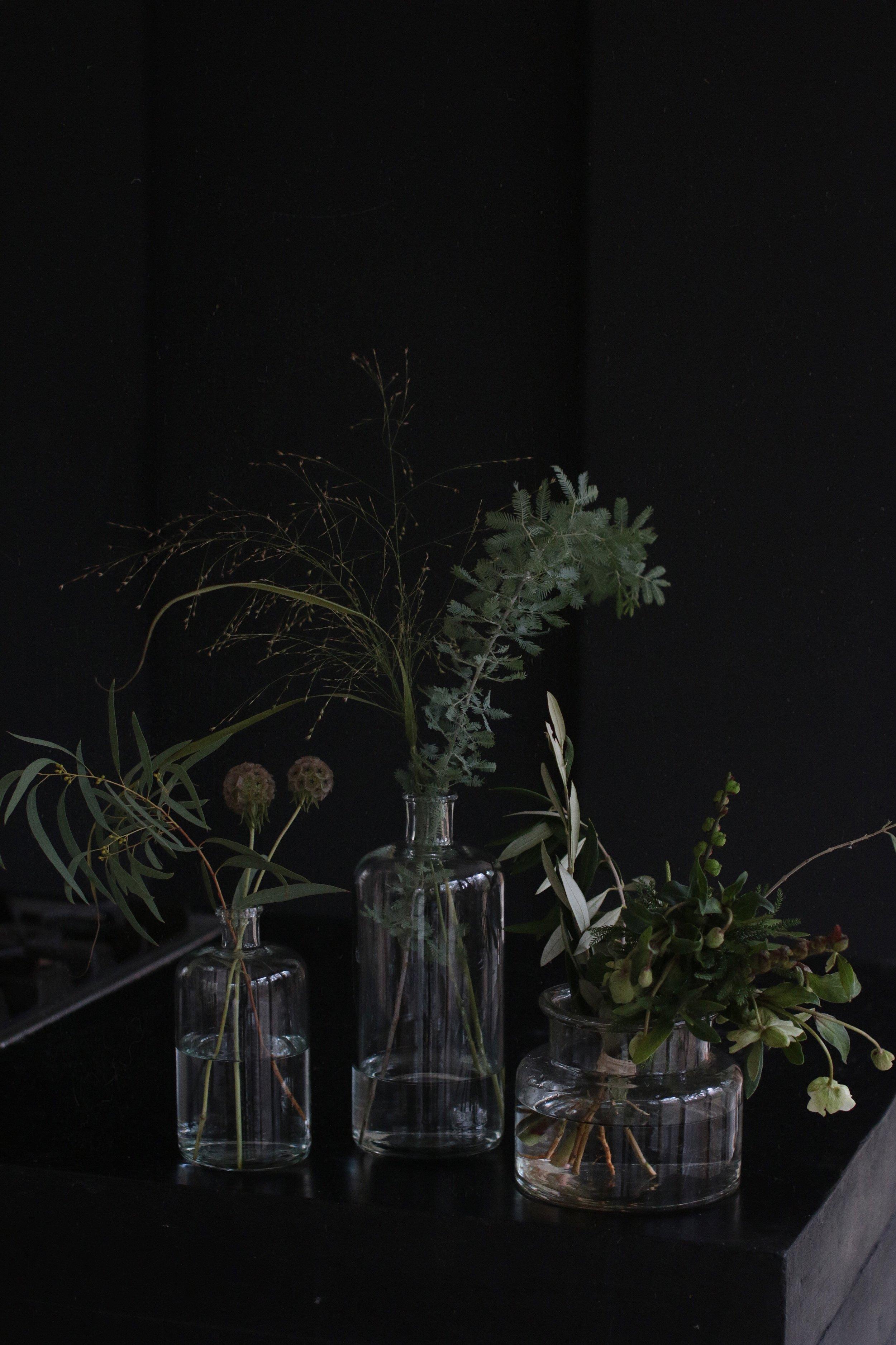 Lasimaljakoita ja pulloja, joissa vihreät kukka-asetelmat.