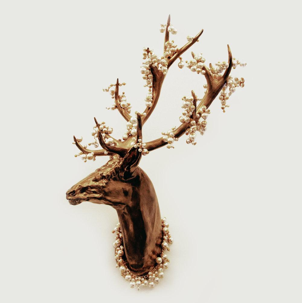Cabeça de veado dourada, de onde brotam inúmeros cachos de pérolas e colar.   A golden deer head and antlers that bear bunches of pearls and necklace.