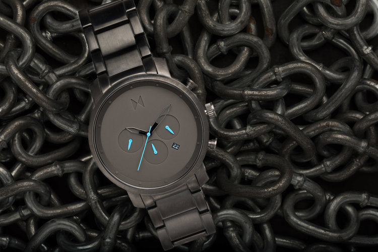 Final image of the MVMT watch with a link chain making up the background
