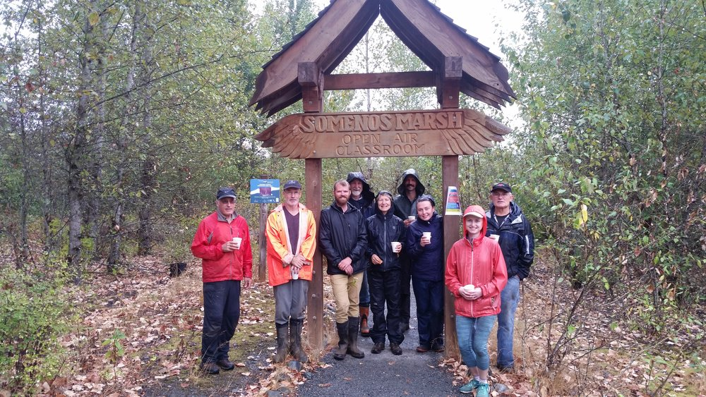 Volunteers pose under the beautifully crafted archway at the Somenos Marsh Open Air Classroom