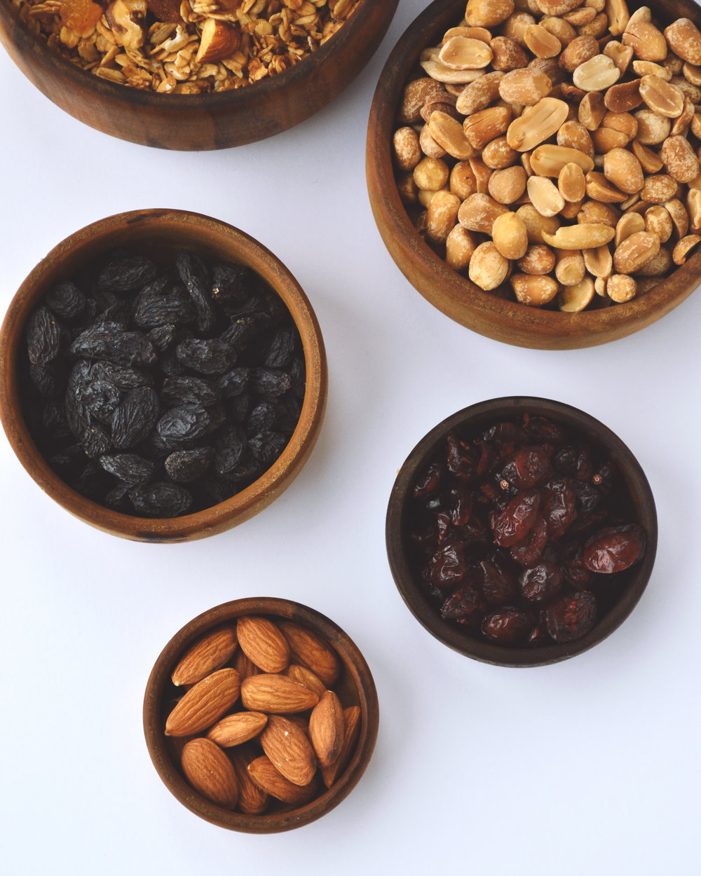 Nuts, cranberries, and raisins in wooden bowls are a healthy component of any diet.