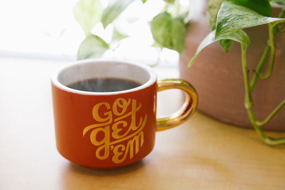 "A mug that says ""go get 'em"" filled with coffee."