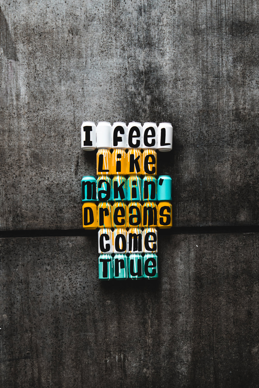 "Cans that spell out, ""I feel like makin' dreams come true"" against a concrete wall."