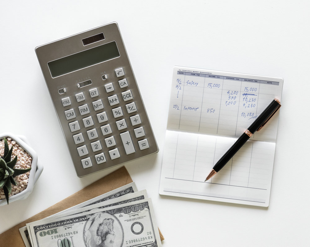 A calculator and a financial notebook for calculating the bills.