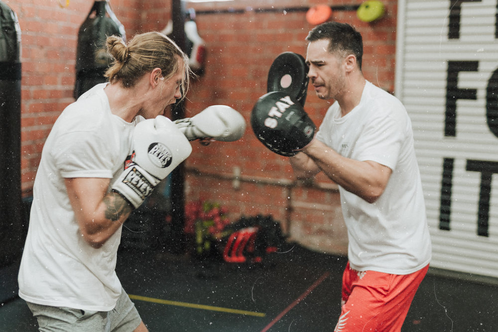 A boxer training with his trainer in athletic clothing.