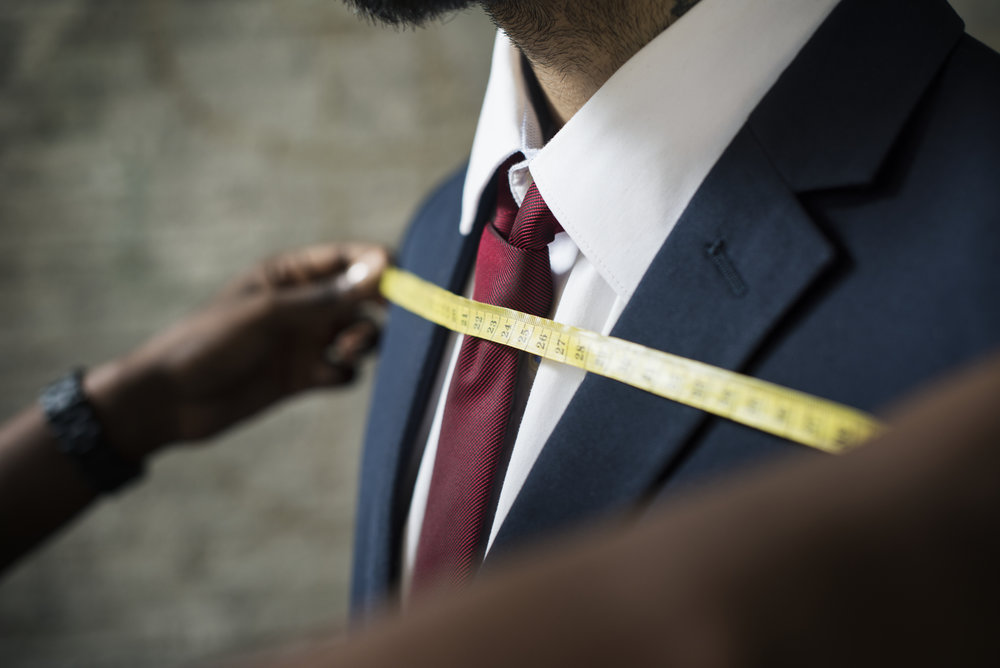 A tailor adjusting the fit of a suit.