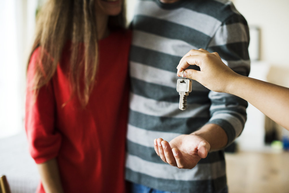 A real estate agent handing a couple a set of keys to their investment.