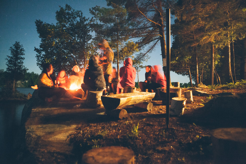 A frugal family camping with a fire in a forest.
