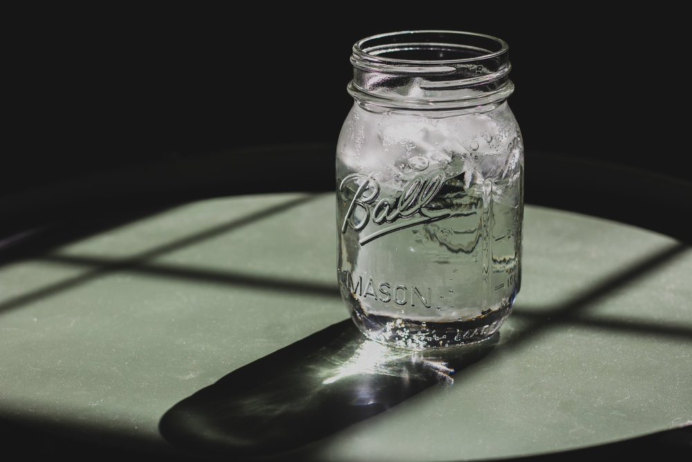 A mason jar filled with water and ready for someone to drink.