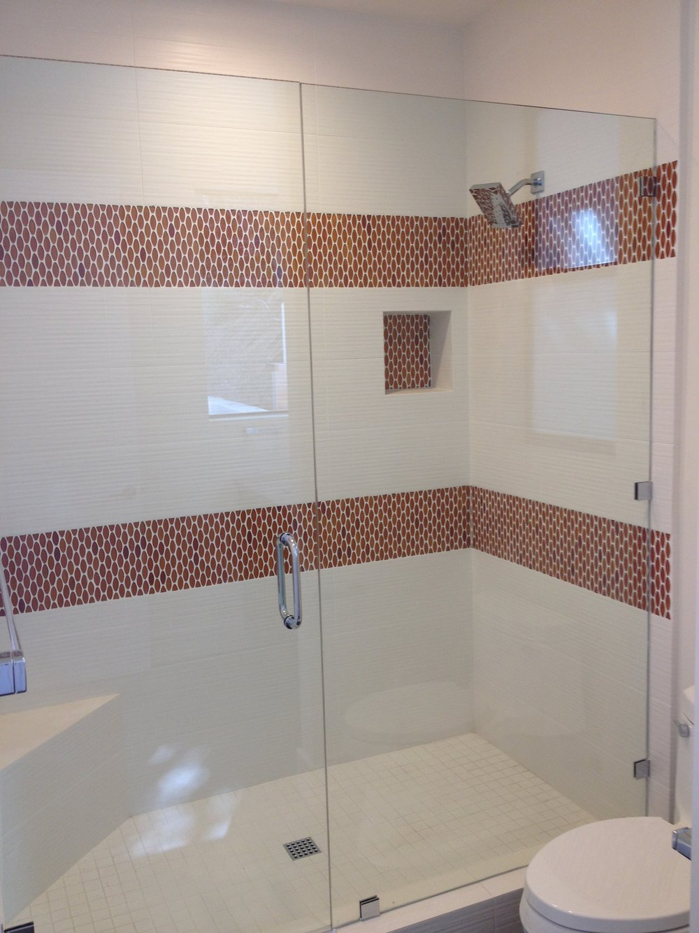 white ceramic tile with orange glass mosaic shower