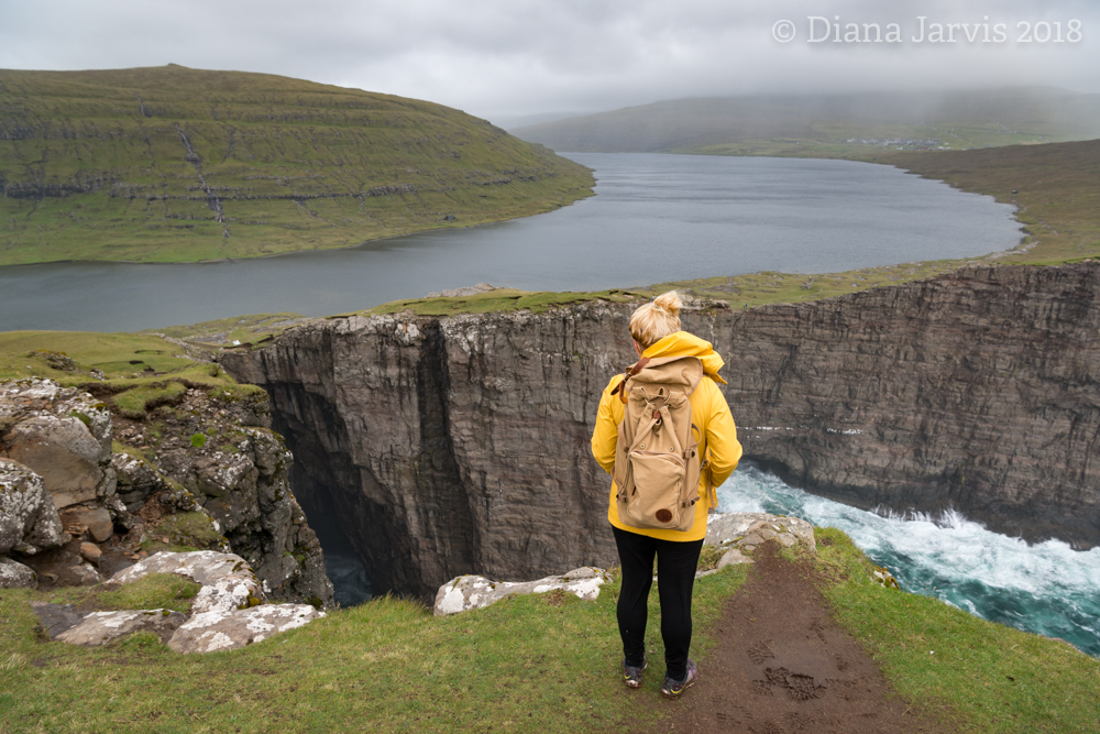 My guide Jana standing at the requisite instagram spot overlooking lake Sorvagsvatn and the sea below