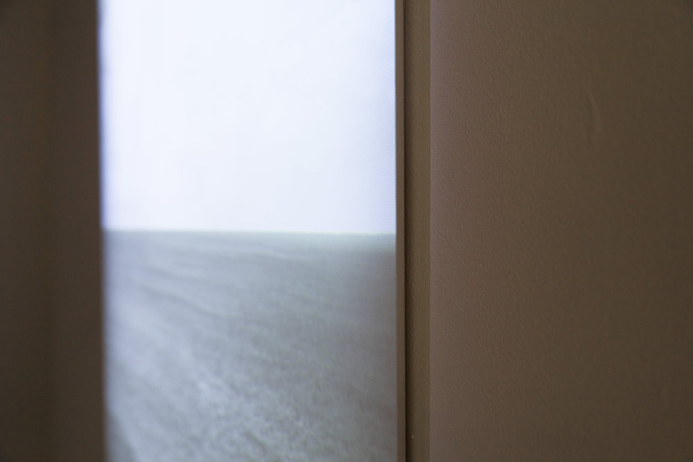 detail of Horizon, video projection on beveled wood panel, 4 minute loop. Video depicts an ocean horizon that slowly gets erased by fast moving storm clouds, leaving only a view of a gray monochrome sky. 2013. collaboration with Carlos Vela Prado