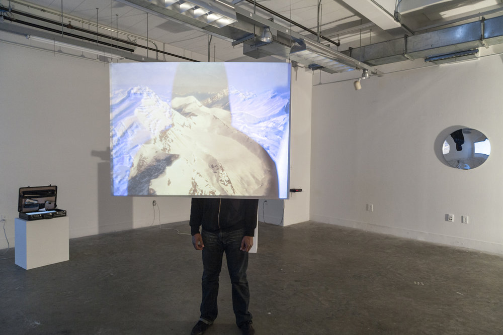(installation view) ' Tupungato',  double slide projectors, slide film, color filter acetate, frosted plexiglass. Dimensions variable.  Each projector cycles through mirroring images of the Tupungato mountain peak, one of the highest peaks of the Andes and the point where my great uncle flew across from Chile. Half of the slides are filtered with color film acetate, so a clear view of the mountain can only be seen in ones own shadow or in that of an onlooker. Collaboration with Carlos Vela Prado