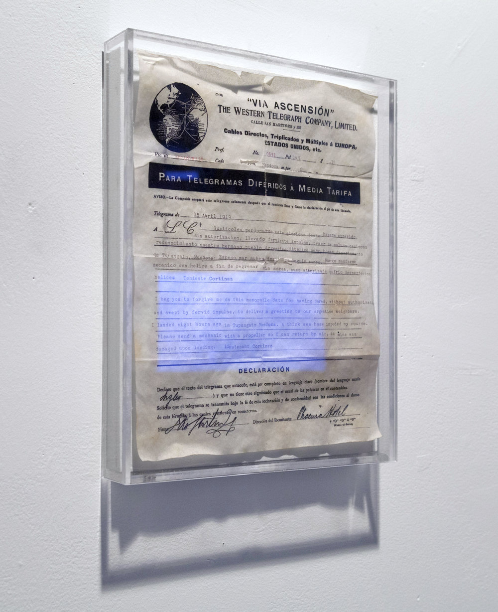 "Via Ascensión (The Western Telegraph) , aged paper and ink in plexiglass frame. 10 x 12""  Fictional replica of the telegraph sent by Cortínez to the Chilean air force upon his arrival in Argentina after successfully crossing the Andes. Collaboration with Carlos Vela Prado"
