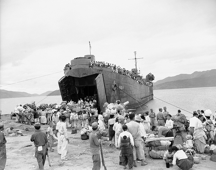 People boarding a ship near Masan, South Korea, in 1950.    PHOTO: JIM PRINGLE/ASSOCIATED PRESS