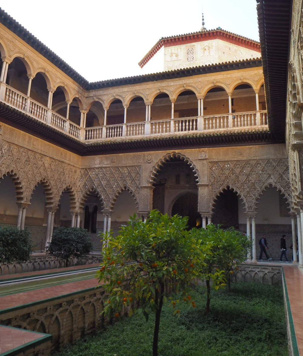 the iconic patio de las doncellas in the mudejar palace was built for king peter of castile; the sunken garden depicted paradise where oranges grew at head height and you could easily pick them without effort. the top floor was built later in renaissance style.