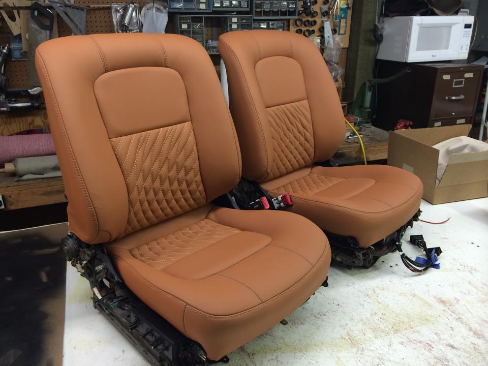 Custom tan leather bucket seats with custom stretched diamond stitching.