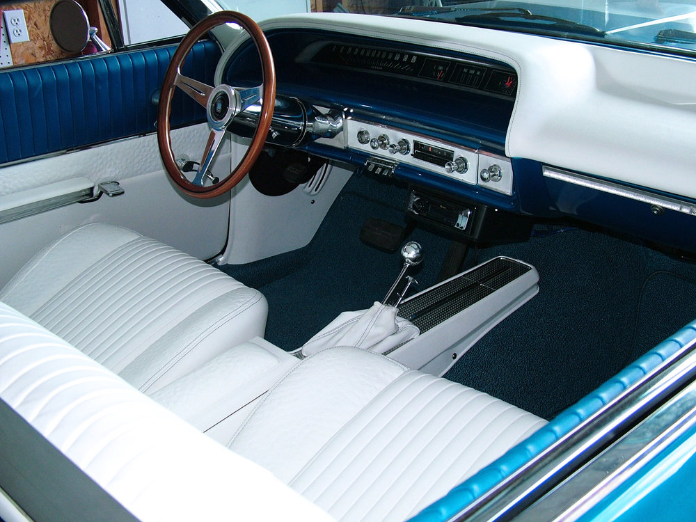 Full custom interior Impala with white leather bucket seats, blue and white door panels, custom white leather wrapped dash, and matching shift boot.