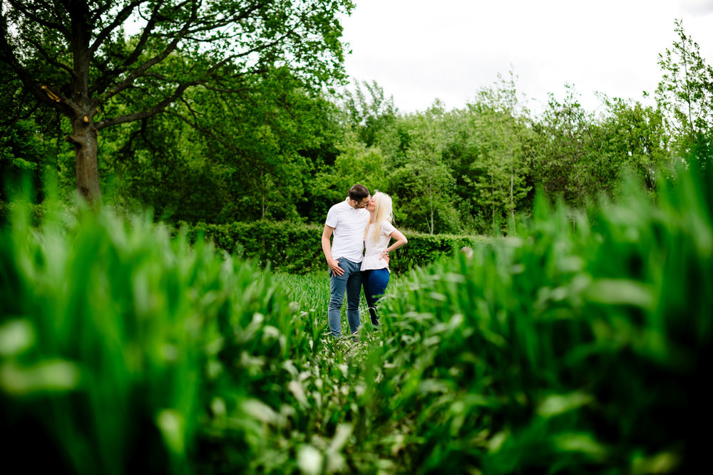 Kissing man and woman stood in a green field