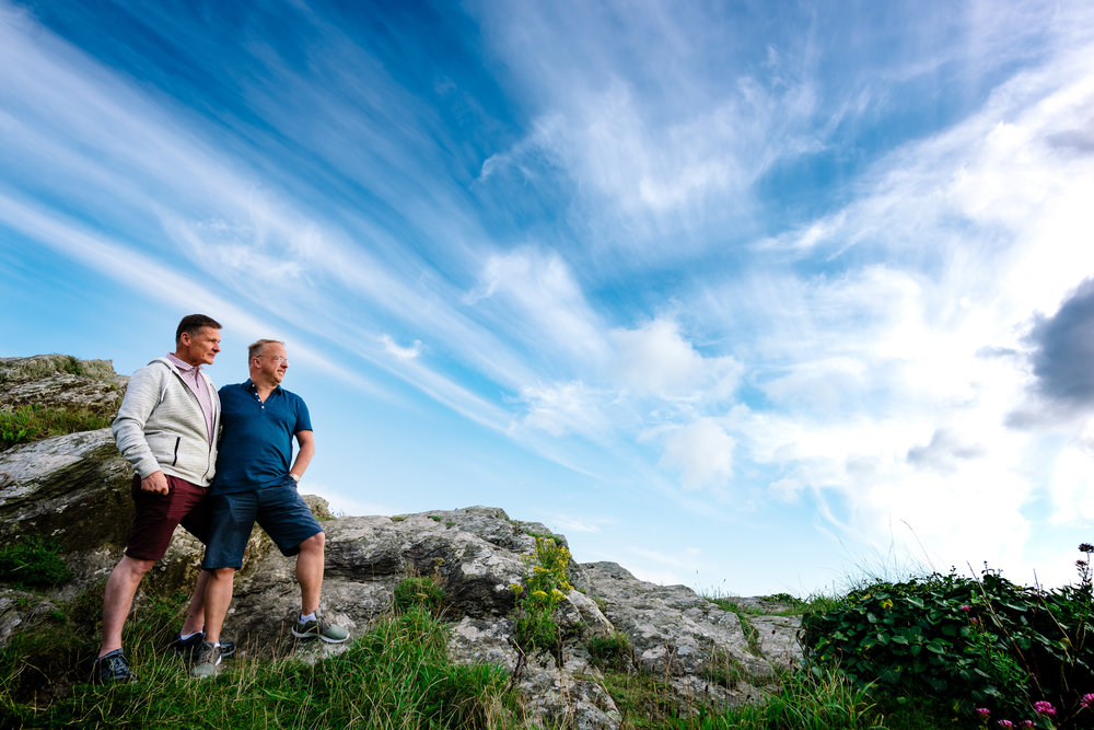 Male couple stood on a mountain looking to the distance