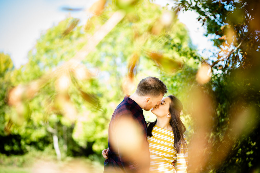 Happy couple kissing outdoors surrounded by Autumn leaves