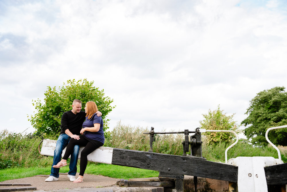 Engaged couple sat on canal lock looking into each others eyes