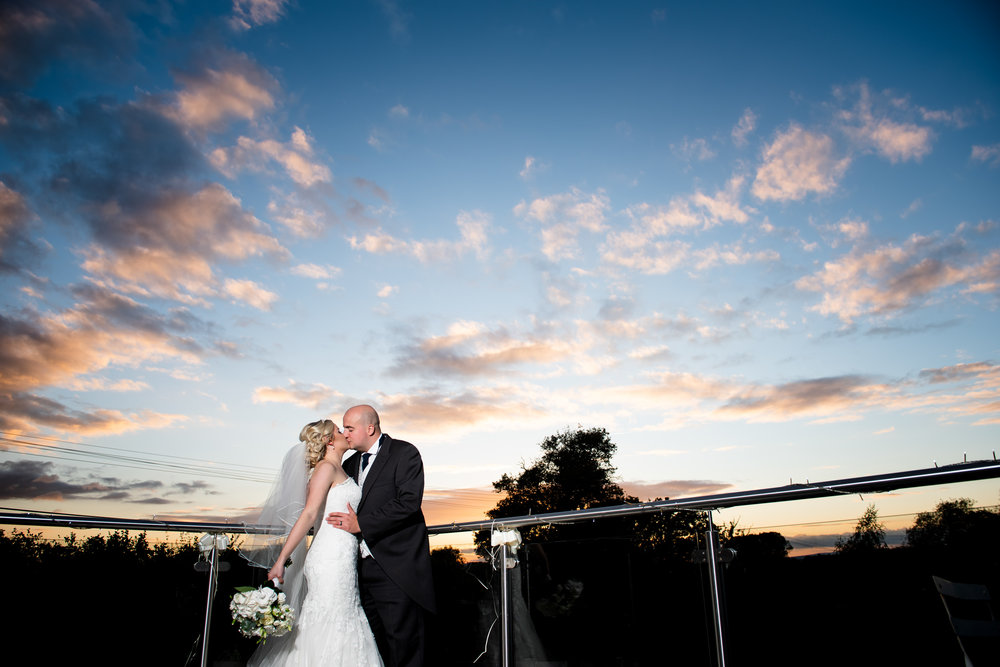 Bride and Groom kissing during twilight on the balcony of Manor Hill House