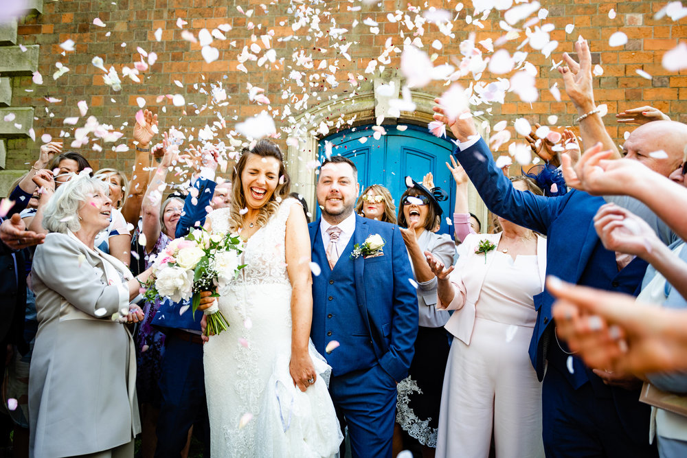 Wedding guest throwing lots of confetti at a laughing Bride and Groom