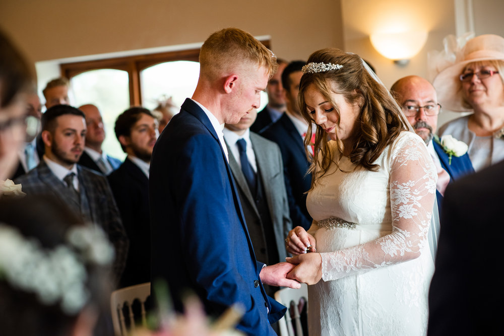 Bride about to place the Wedding ring on the Groom during a Wedding ceremony at Bordesley Park Farm Worcs