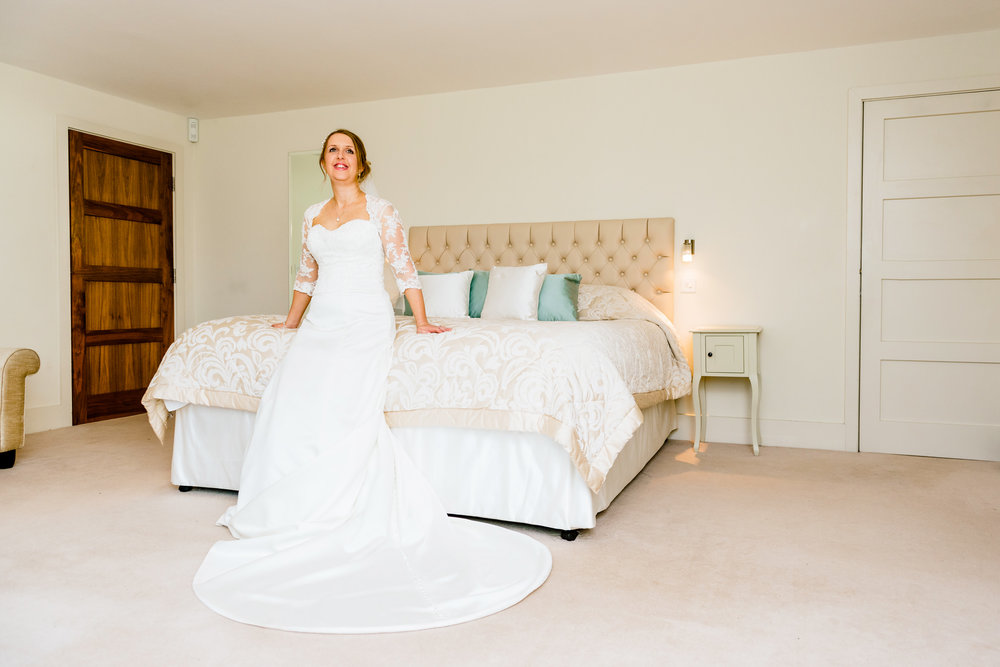 Smiling Bride posing sat on a bed at Manor Hill House Worcs
