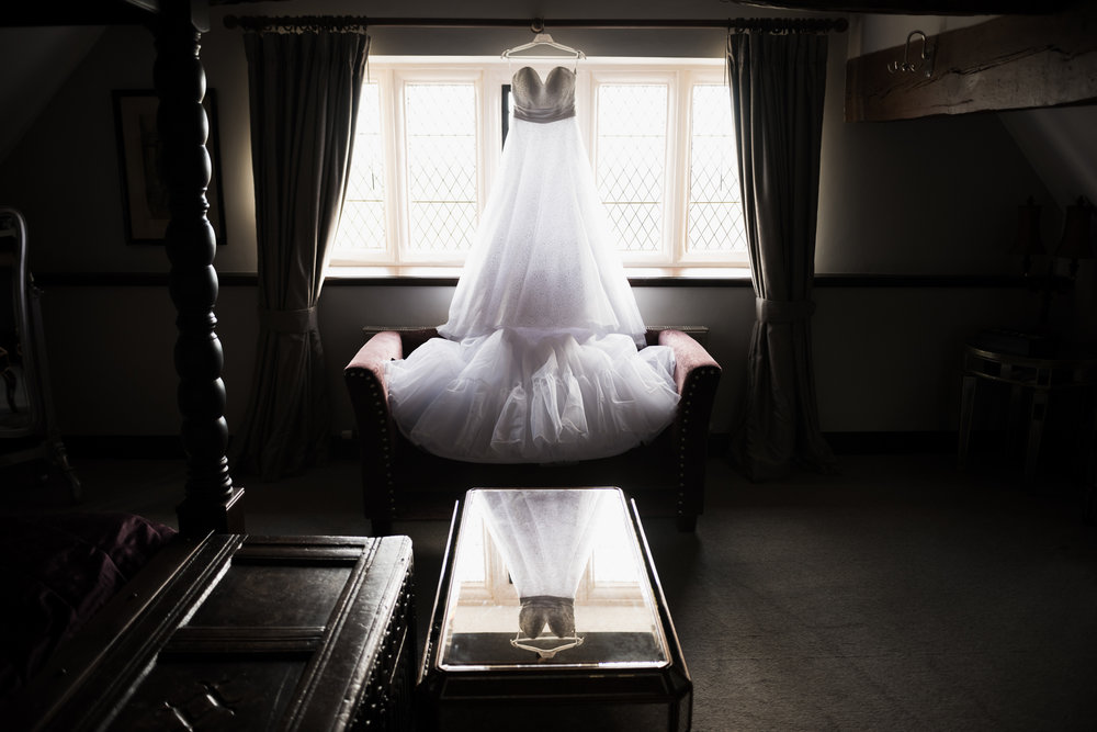 Atmospherically lit Wedding dress hung in front of a Bridal suite window at Weston Hall