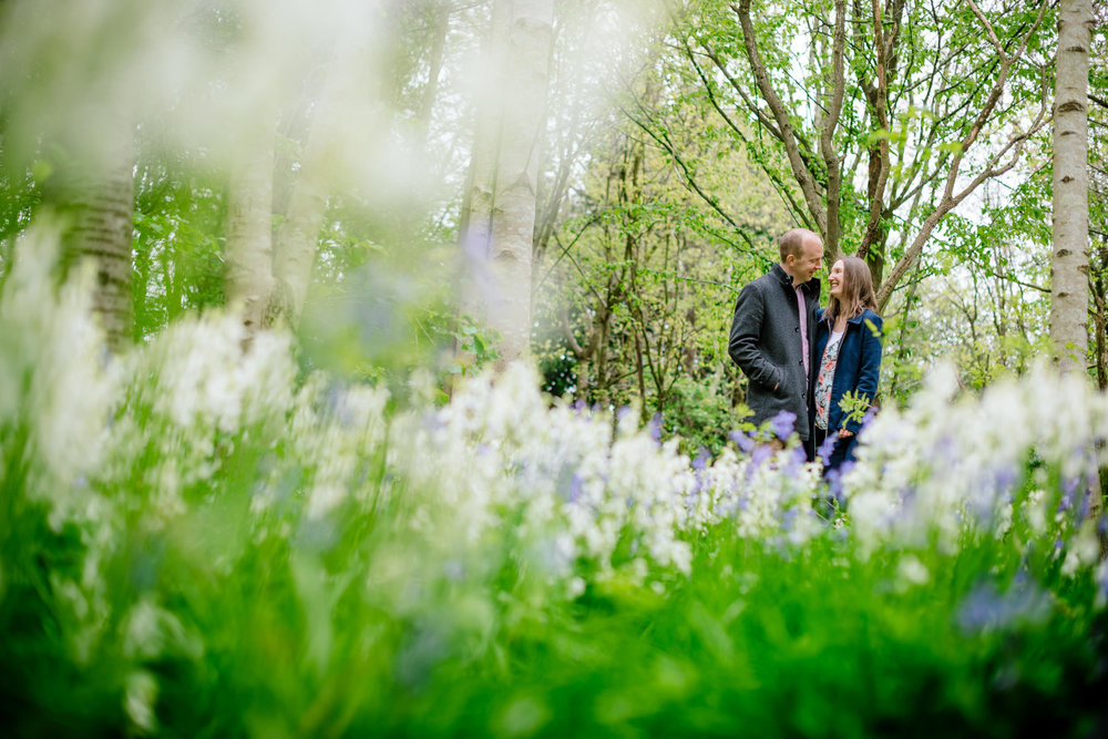 Couple looking at each other in a white bluebell wood