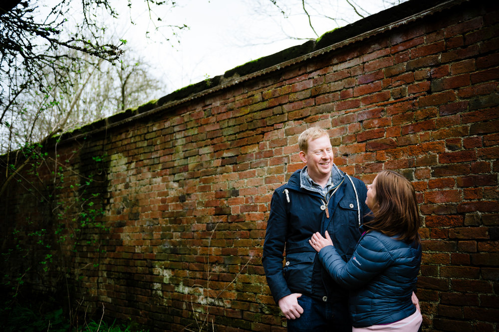 Woman holding man while man is laughing next to vintage brick wall