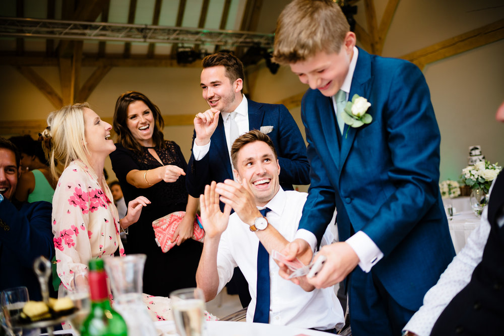Young boy performing magic tricks for other guests during the Wedding breakfast