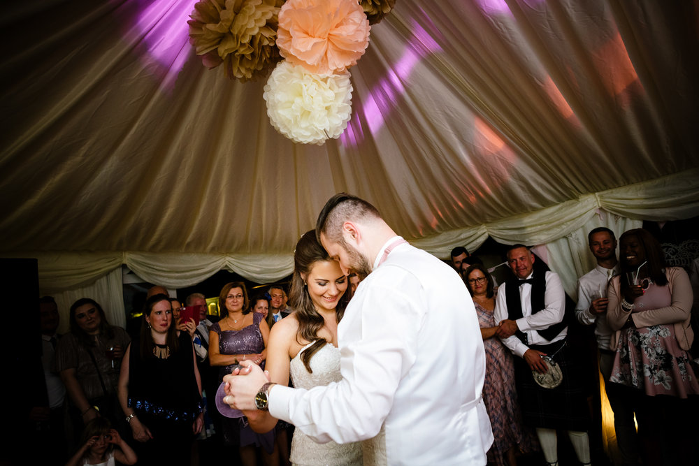 Bride and Grooms romantic first dance with guests watching in the back ground
