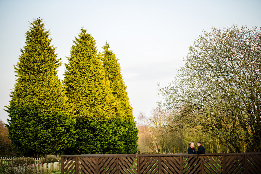 Same sex couple on a wooden bridge at The Abbey Hotel Redditch