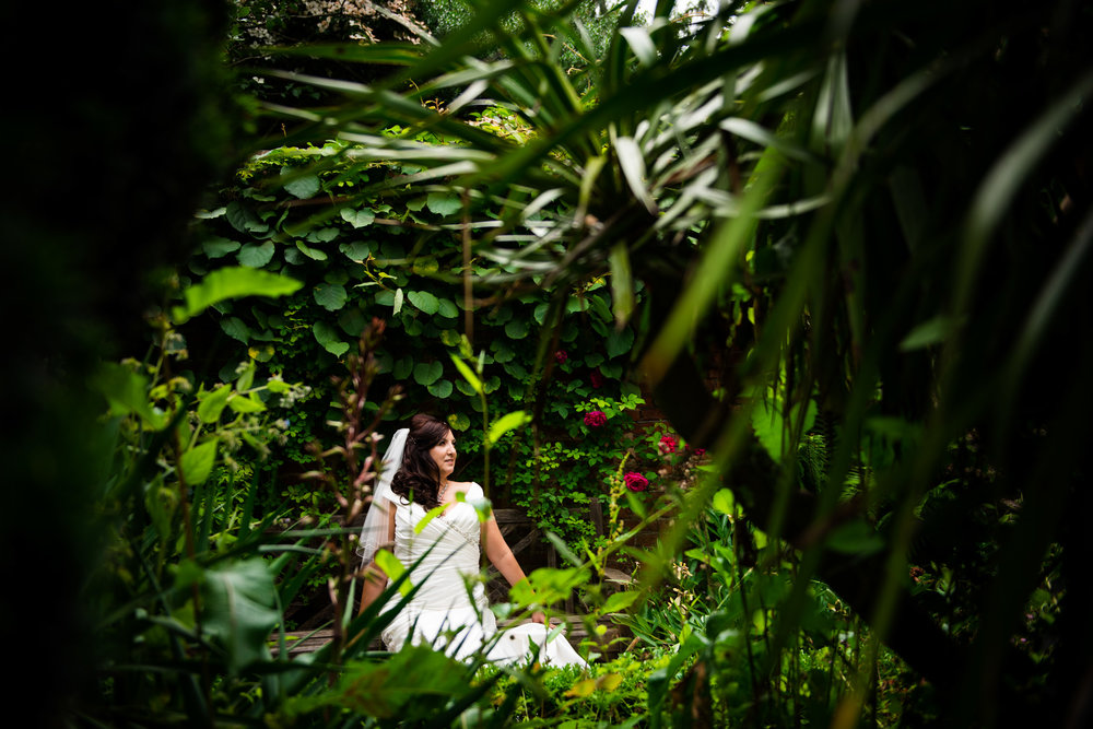 Portrait of a bride in the middle of bushes in a beautiful garden