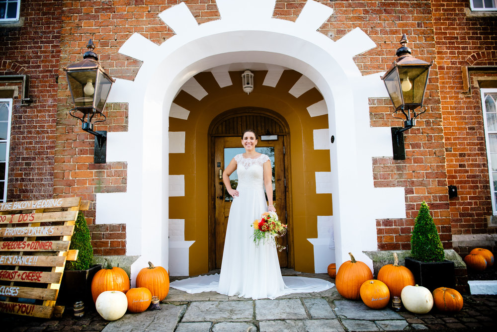 Bride in Arrow Mill enterance surrounded by Pumkins for Halloween themed wedding