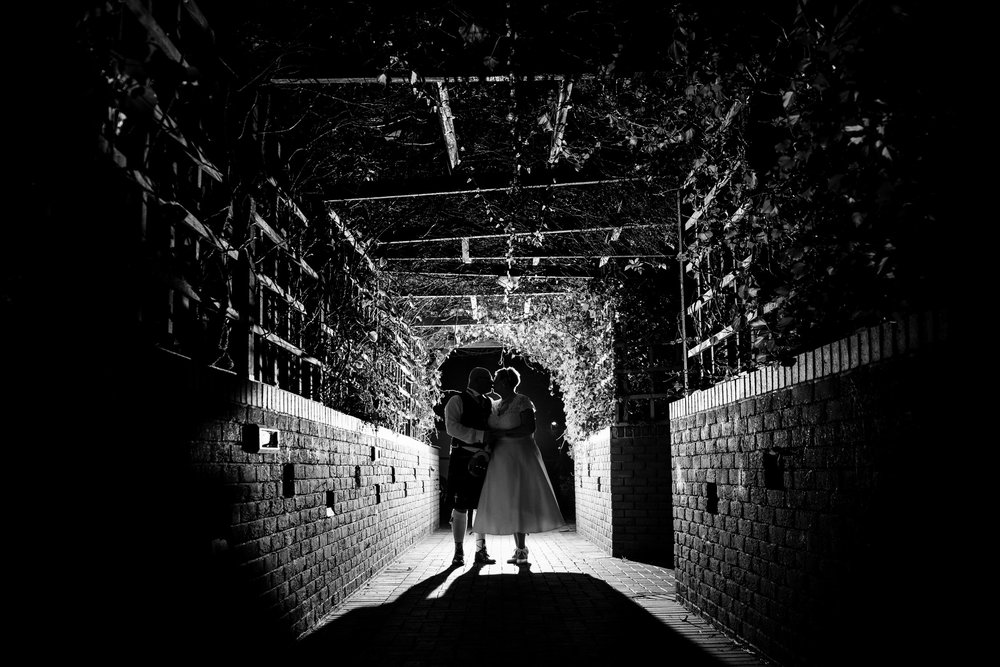 Silhouette of Bride and Groom kissing under a foliage archway at the Abbey Hotel, Golf and Spa