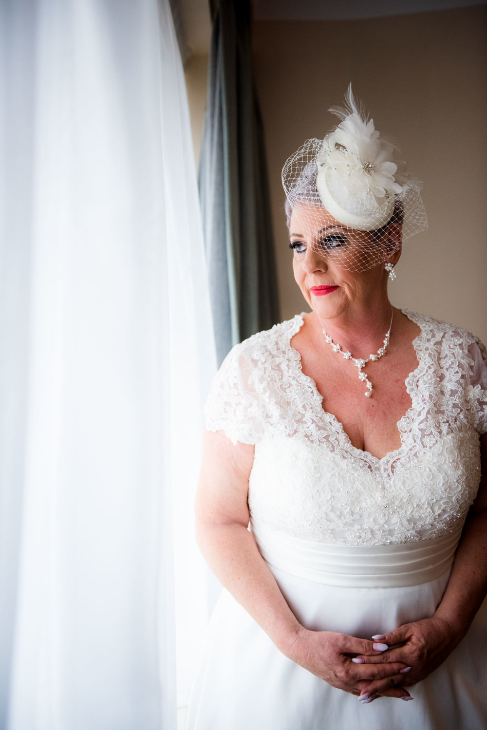 Stunning Bride after putting on the wedding dress looking out of the window